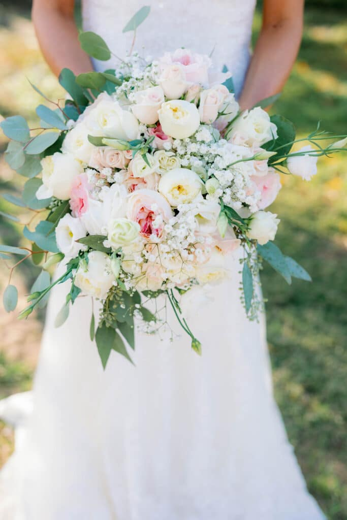 flower bouquet held by a bride on her wedding day, featuring several types of white and pink flowers