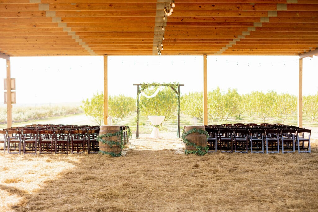 wedding ceremony area at Southern Hill Farms set up in a covered pavilion with straw covered floor