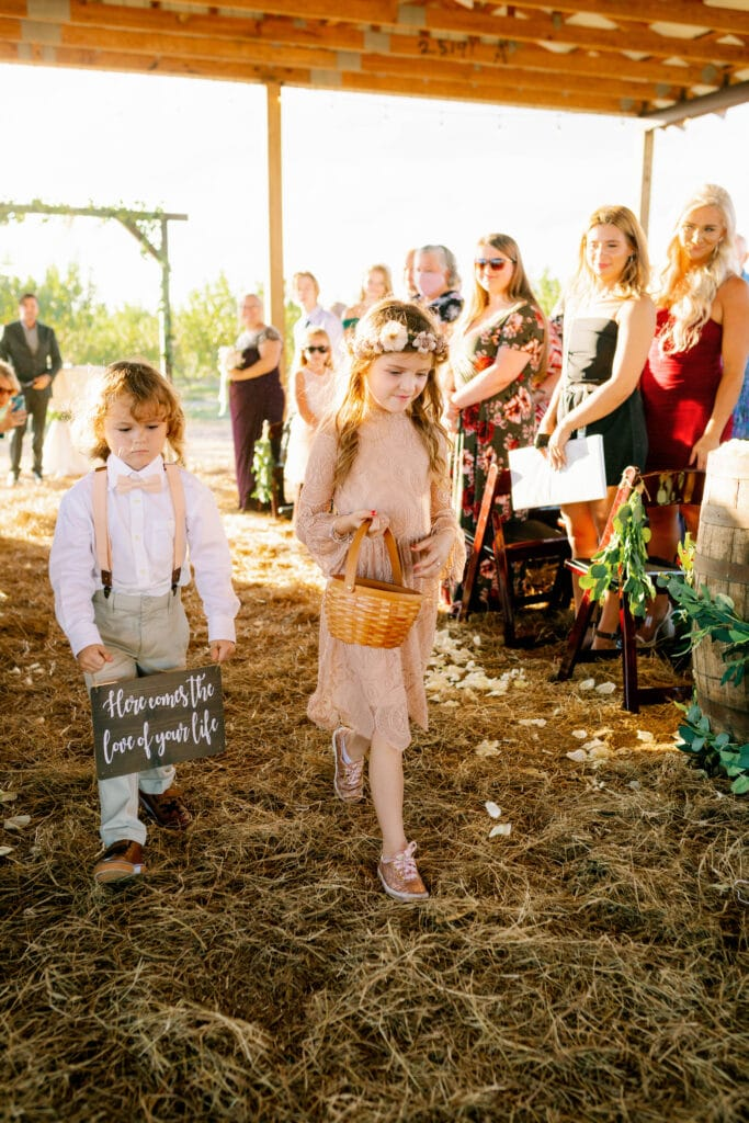 flower girl and ring bearer walking down the aisle during a wedding ceremony at Southern Hill Farms