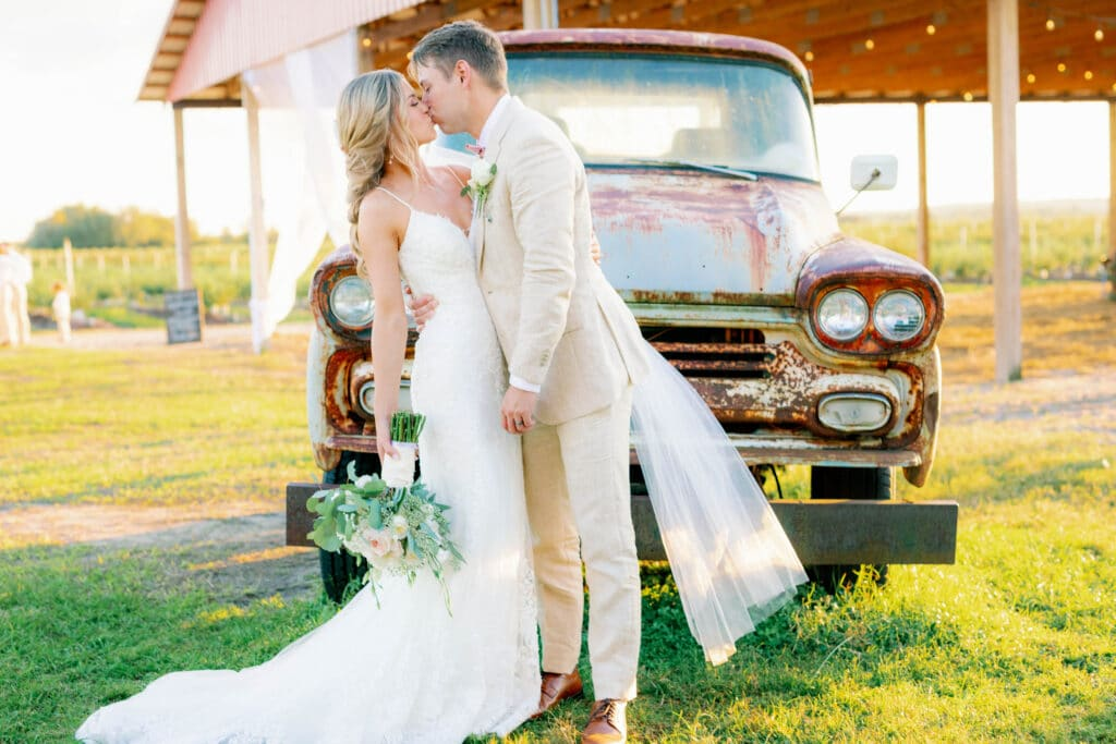 bride and groom kissing in front of rustic pickup truck featured at Southern Hill Farms