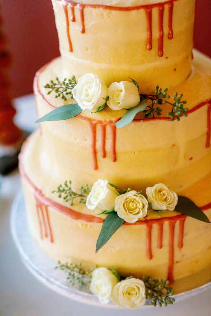 three tiered wedding cake decorated with white roses