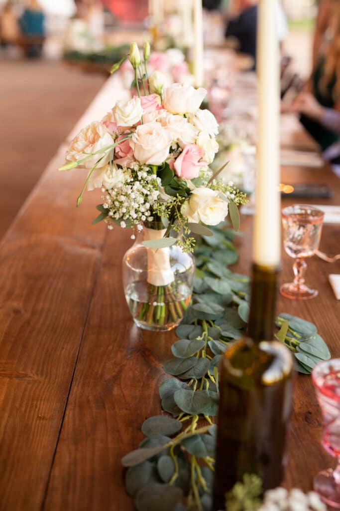 long wooden tables set up for wedding reception decorated with white and pink flowers, white candles, and pink glasses