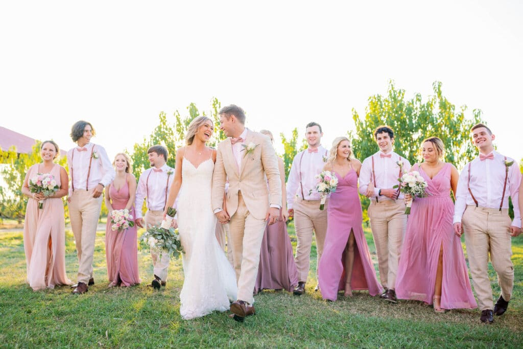 bride and groom walking hand in hand while their bridal party walks in a line behind them