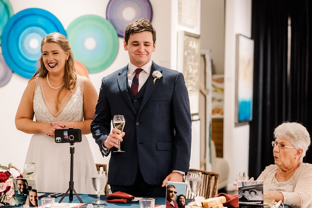 newlyweds stand up at reception table for toast smiling with phone on tripod on the table in front of them