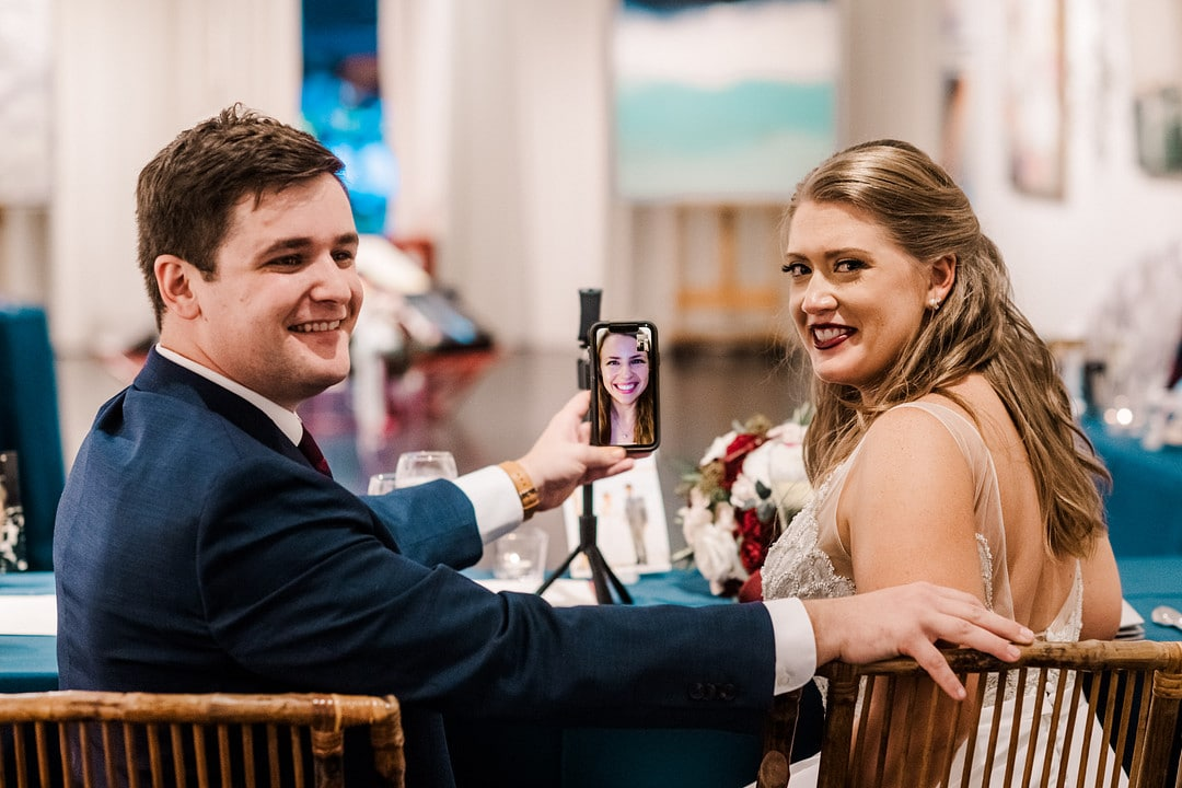 bride and groom turn around to look at the camera while sitting at wedding reception table with camera video chatting someone in front of them