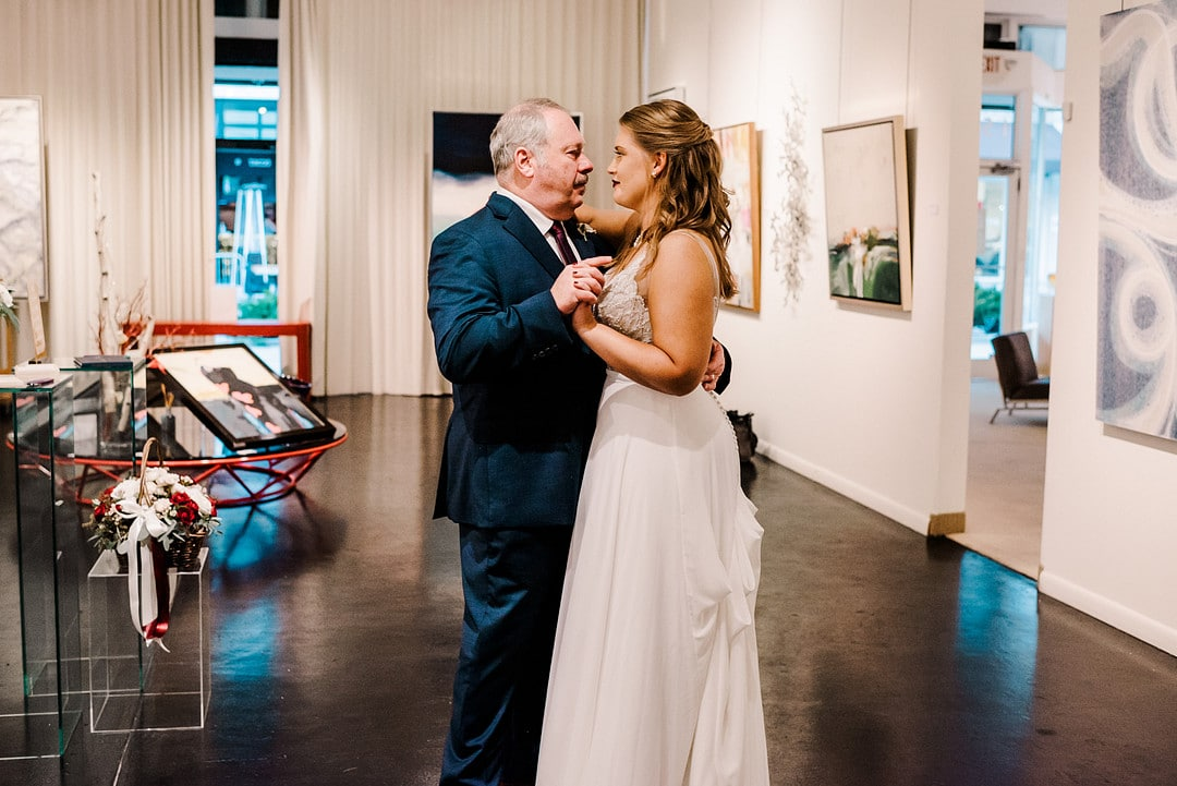 bride dances with father on wedding day in art gallery