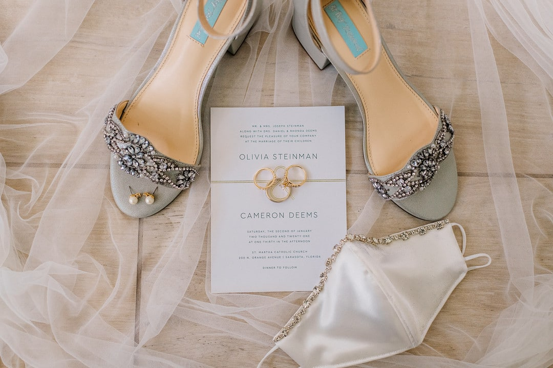 detail picture of brides accessories including rings heels earrings wedding day face covering and veil