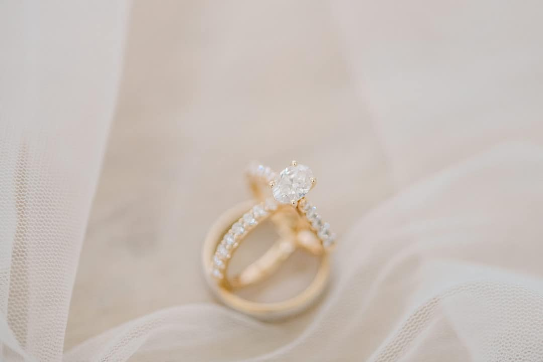 close up of gold wedding rings and engagement rings sitting on the brides veil