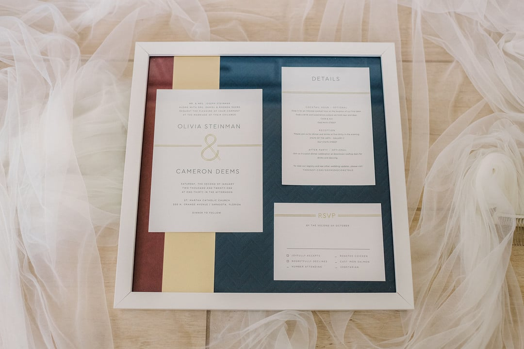 invitation and rsvp card and details card in frame together with colors of the wedding photographed on top of brides veil