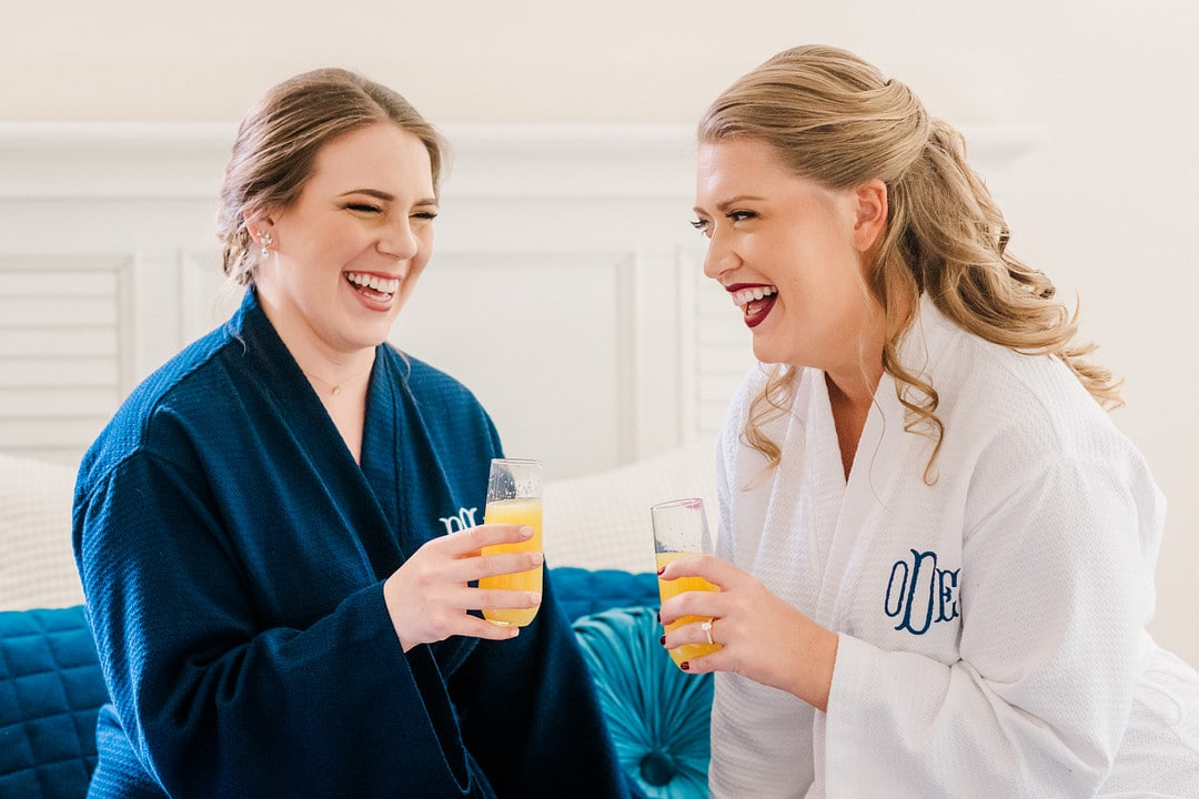 bride wearing white custom robe sits next to another woman wearing navy blue custom robe both holding mimosas and laughing next to each other