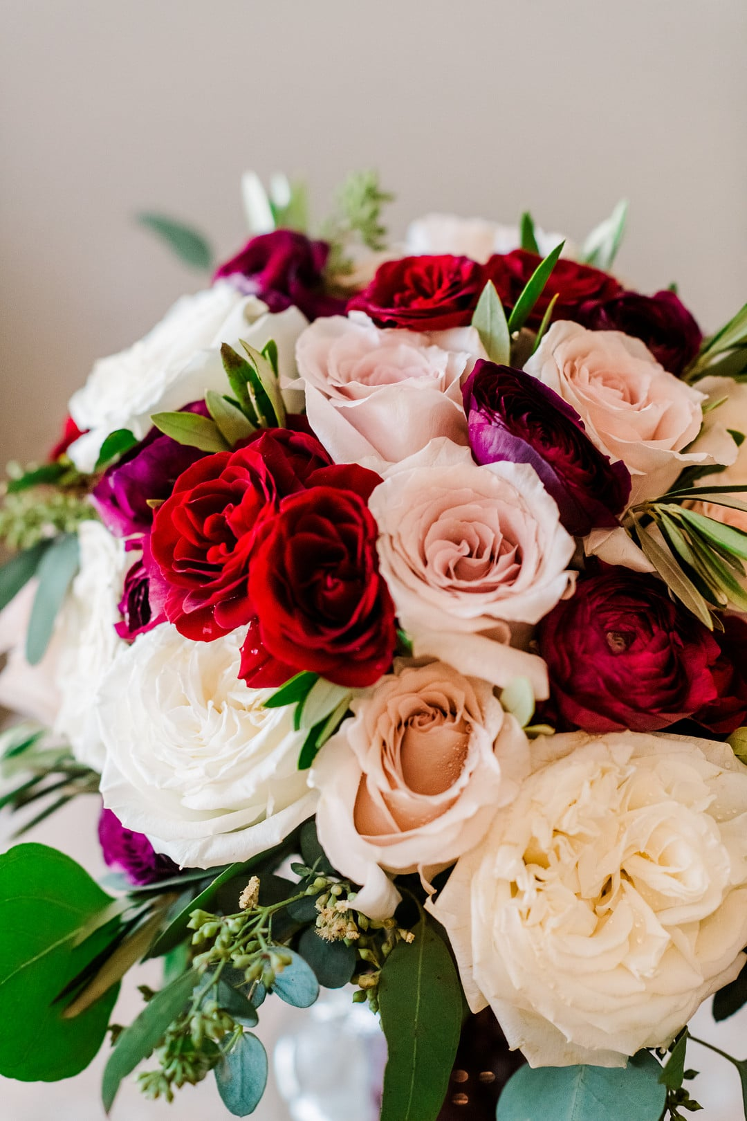 bridal bouquet with red pink and white flowers and some greenery in it
