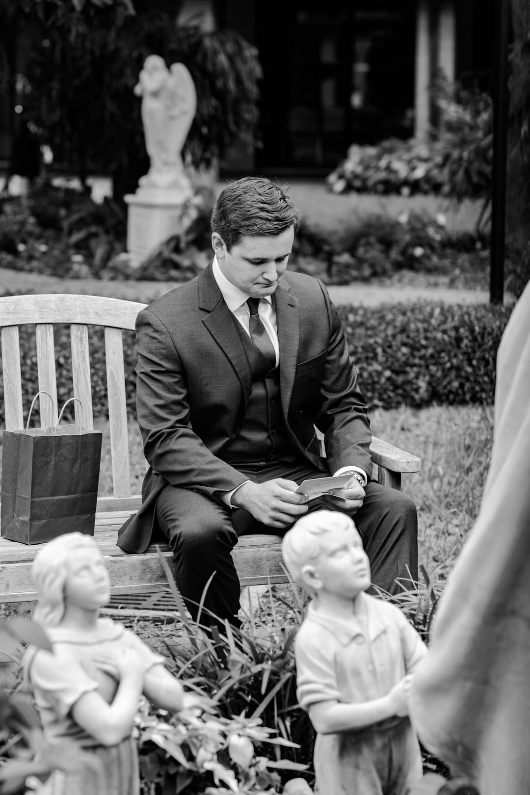 black and white image of groom sitting in garden on a bench looking at letter with statues in front of him