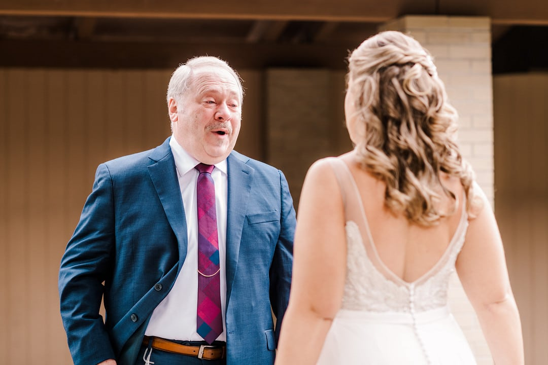 surprised father wearing navy blue suit has first look with daughter at winter beach wedding day