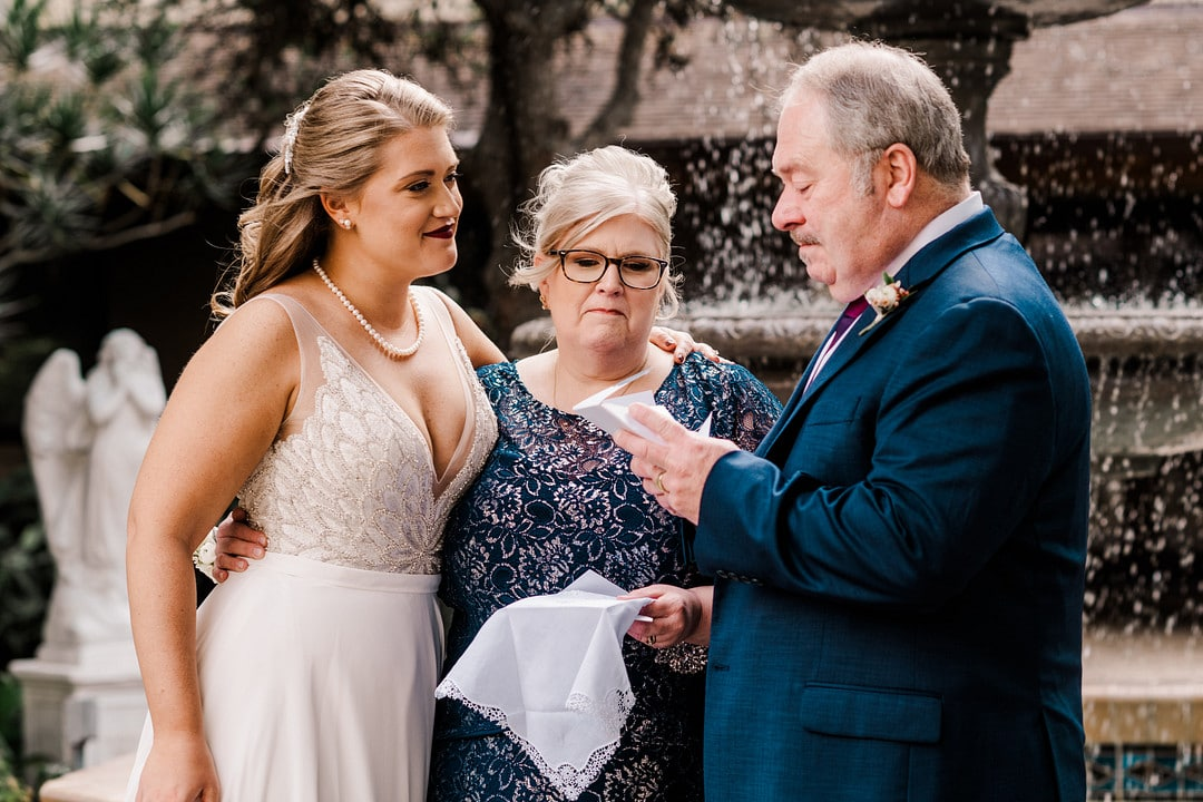woman on wedding day stands with her parents while father looks at gift in his hands in front of fountain