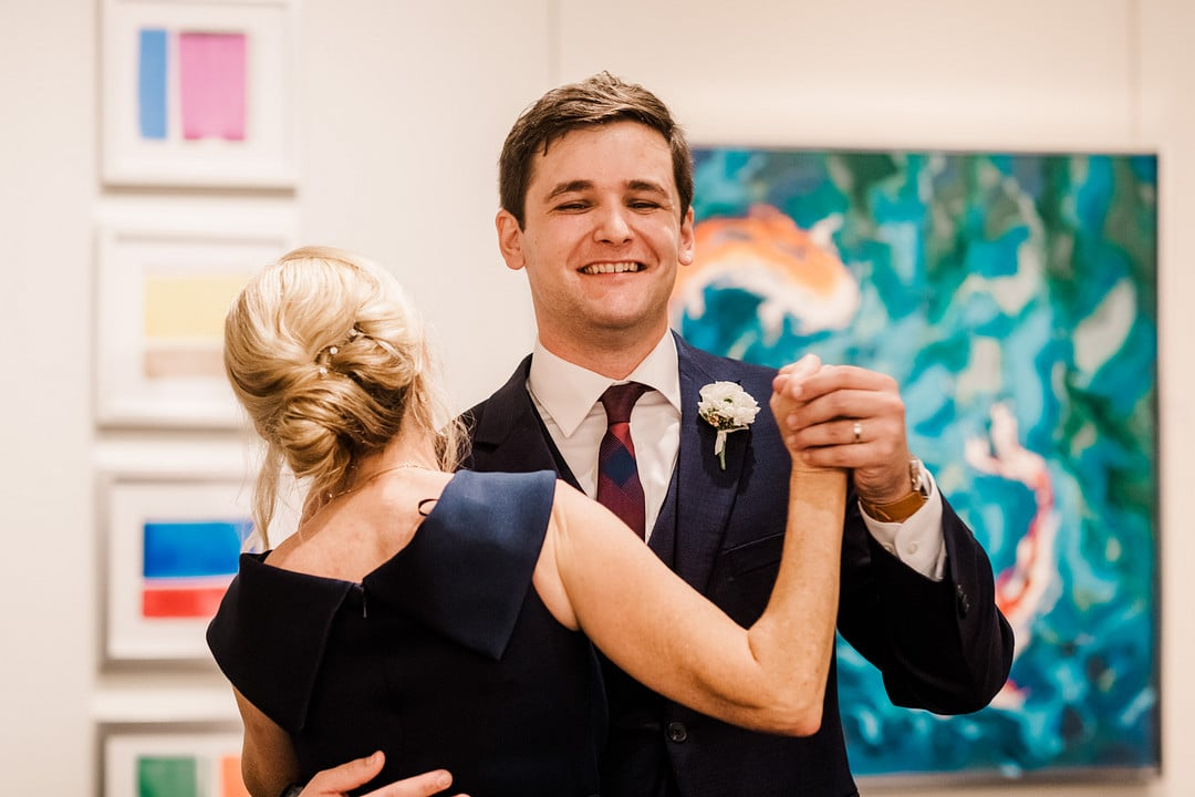 groom smiles while dancing with mother in front of artwork on wedding day
