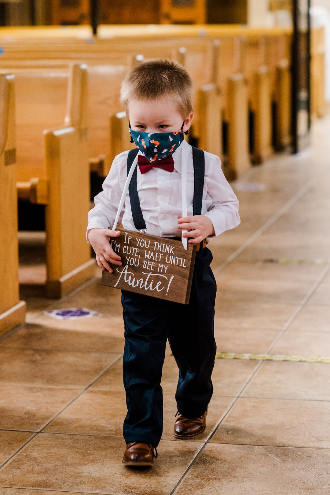 ring bearer wears wooden sign wearing suspenders walking down the aisle in church with mask on