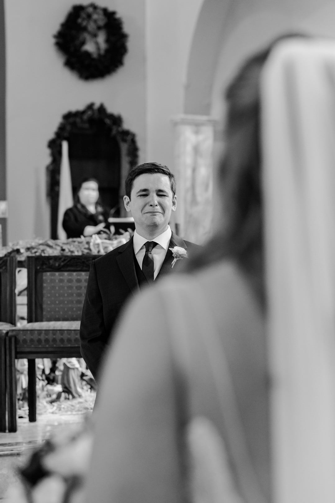 black and white image looking over brides shoulder as groom sees bride come down the aisle crying