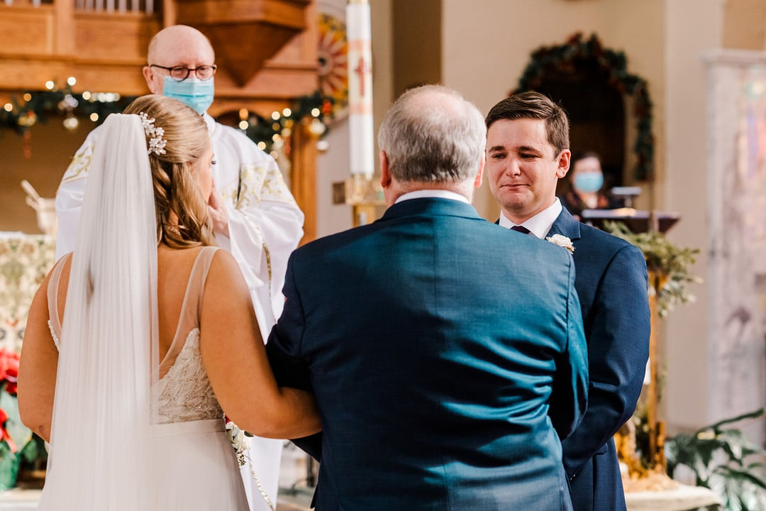bride and father stand linked by arms in front of altar while groom looks at bride with emotion filled expression