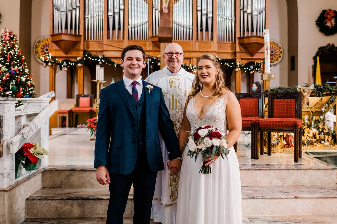 newlyweds stand holding hands at altar in front of the officiant who married them in catholic churches