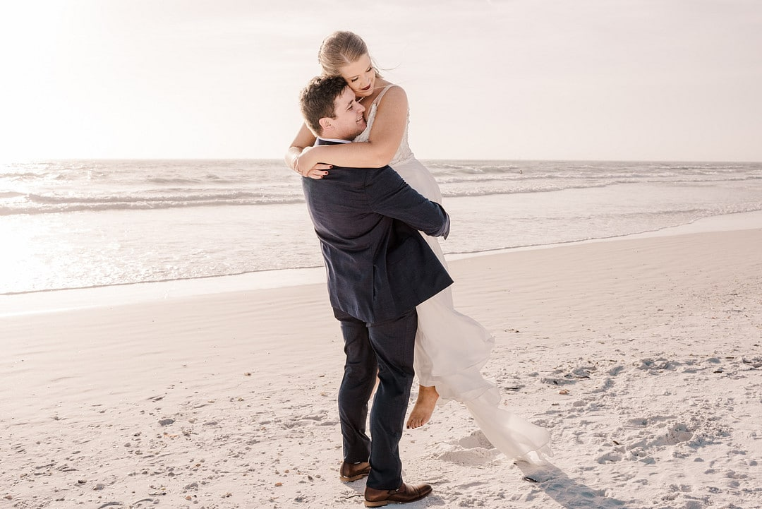 groom lifts bride up in the sand at winter beach wedding day