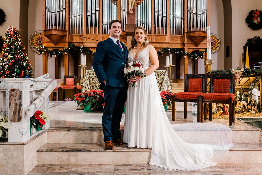 newly married couple stand together while bride holds her bouquet on wedding day at the altar of catholic church decorated for the holidays