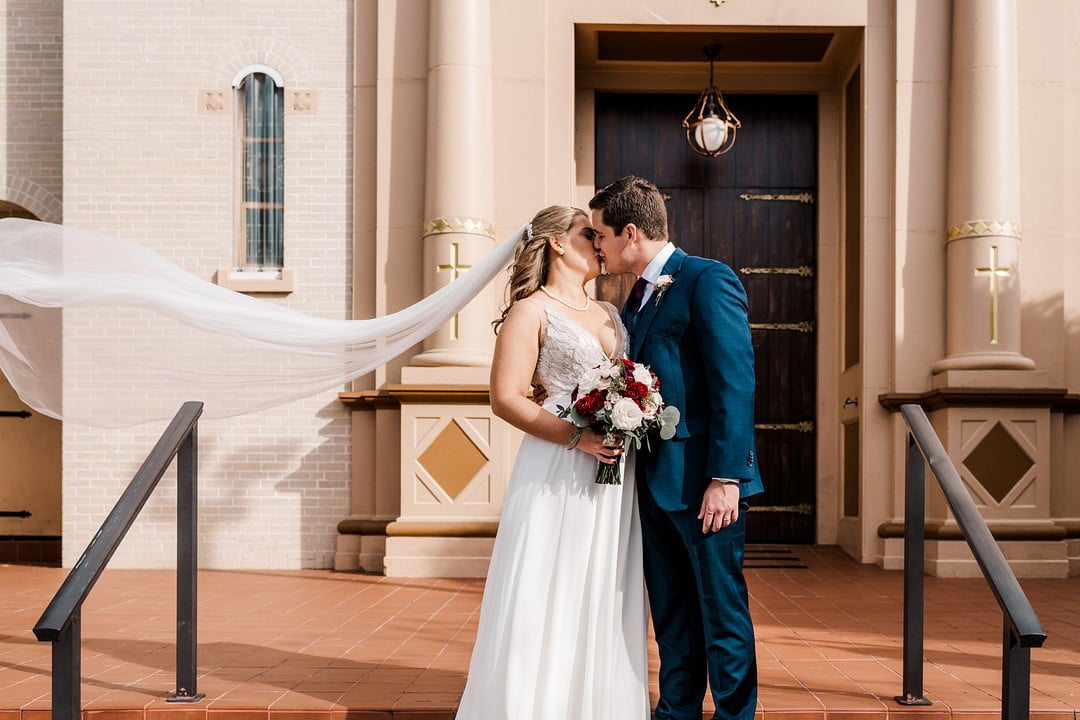 bride and groom kiss on steps of church while holding bouquet and veil floating in the air behind her
