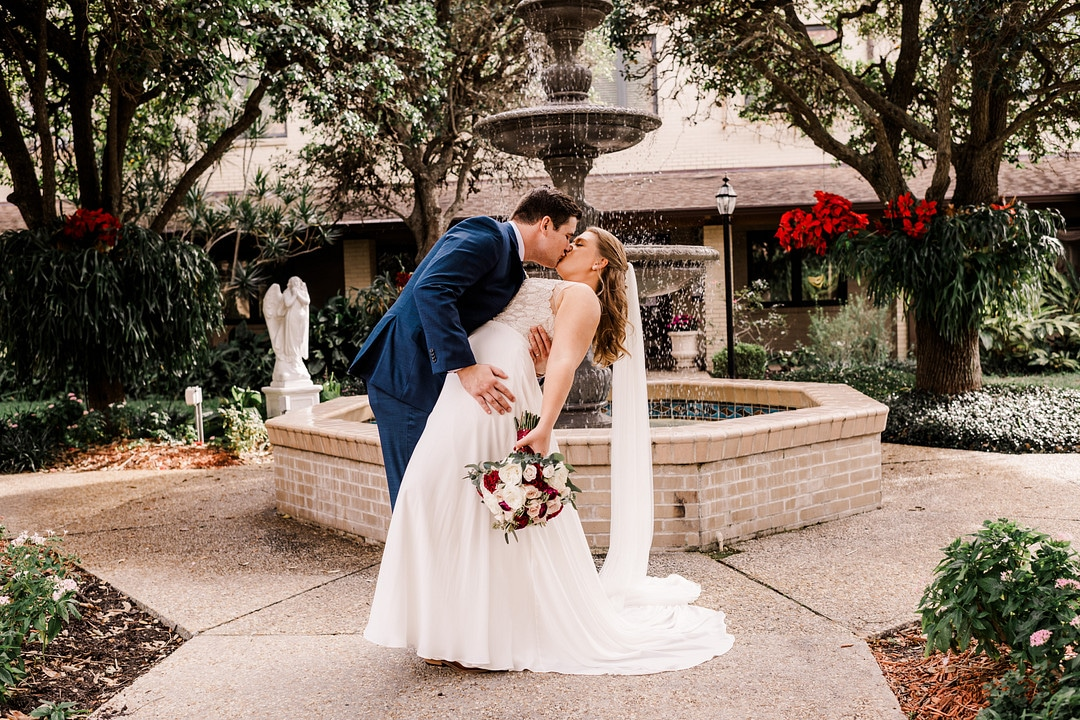 husband dips wife down while holding her bouquet on wedding day in front of fountain outside