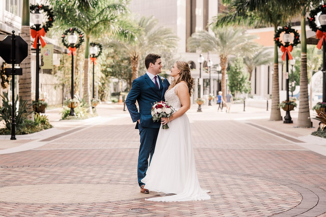 bride and groom stand together outside downtown with lightposts decorated with christmas wreaths and palm trees in the background