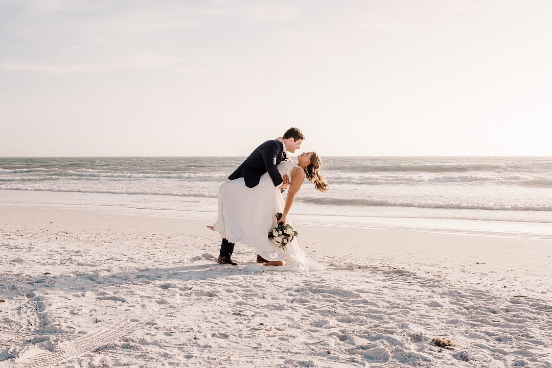 groom dips bride down while she holds her bouquet in the sand on the beach in front of the ocean