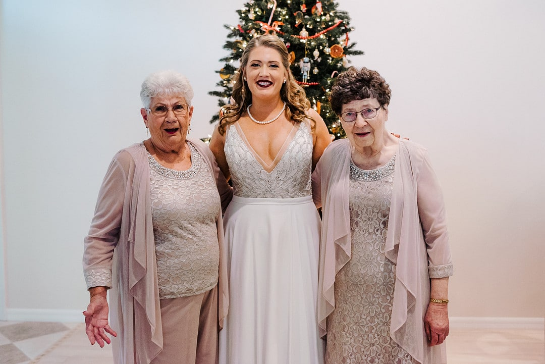bride on wedding day with two grandmothers on both sides of her and christmas tree in the back