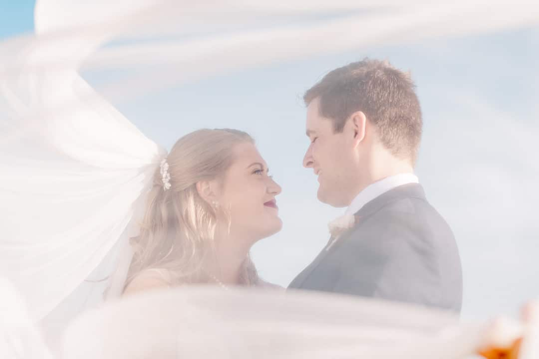 looking through brides veil a couple stands smiling facing each other