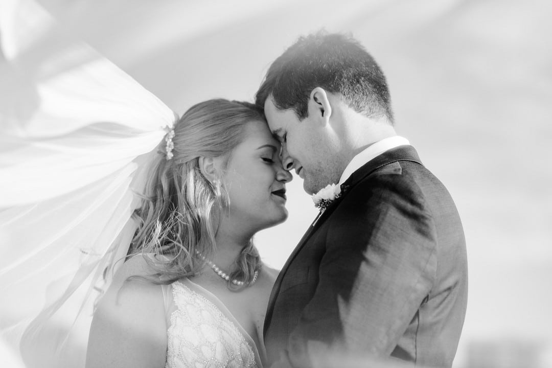 black and white image of couple on wedding day touching foreheads with veil floating in the air around them