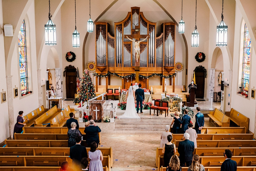 catholic church with couple at altar being married an a few guests in the pews watching
