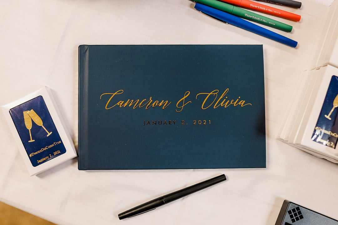 navy blue guest book on white table clothe with colored pens above and below it with the couples names on the front in gold script font