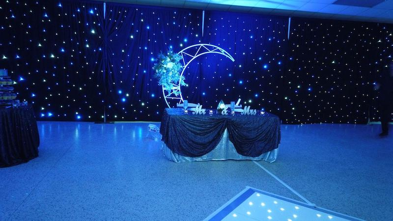 wedding reception decorated with space theme, including lights for stars along the walls and a moon backdrop