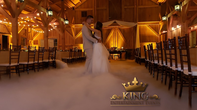 bride and groom dancing in the middle of their wedding reception as fog lines the floor