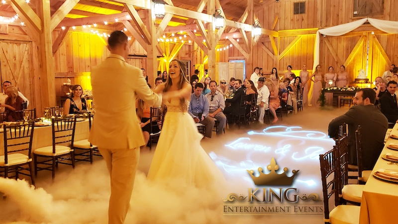 bride and groom laughing while sharing their first dance and fog fills the dance floor