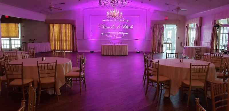 wedding reception set up with large dance floor and purple uplights set up behind the sweetheart table