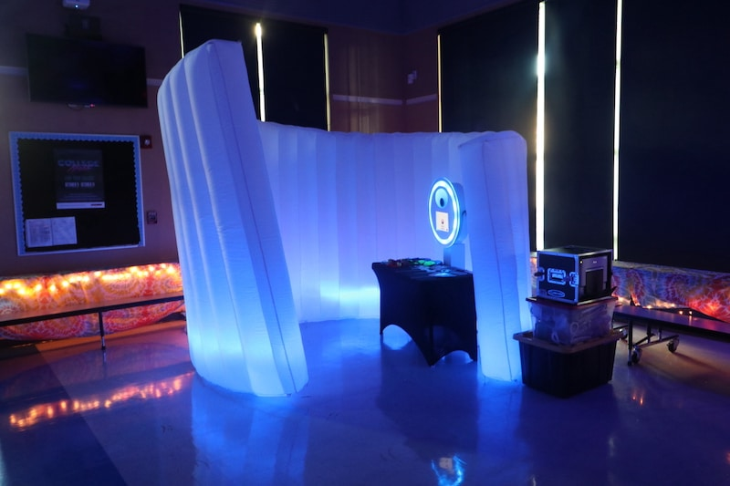 photobooth set up with a white blowup backdrop and blue lights