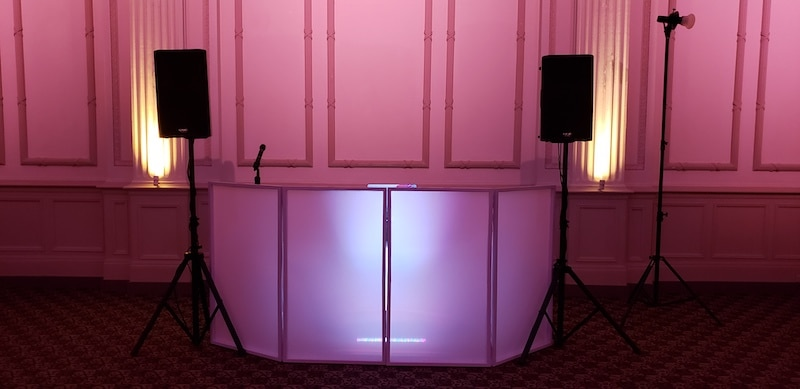 dj facade backlit with white light and two speakers on either side