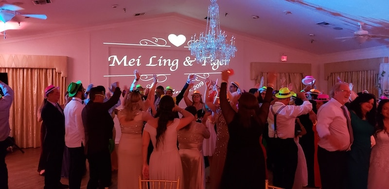 guests partying on the dance floor all wearing funny hats