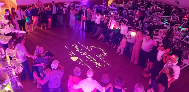 guests dancing in a circle while bride and groom's name is shining on the dance floor