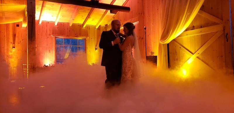 bride and groom dancing at their wedding reception with fog along the floor