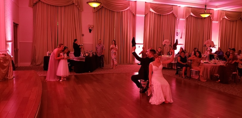 bride and groom sitting on chairs in the middle of the room playing the shoe game