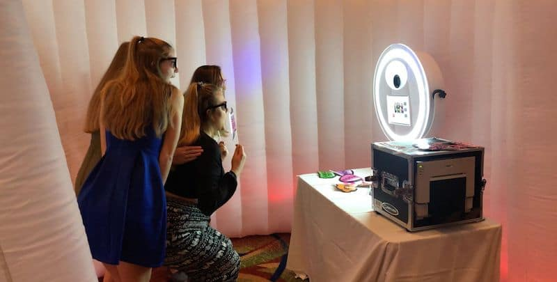 women taking pictures with a photobooth set up inside of white blow up screen