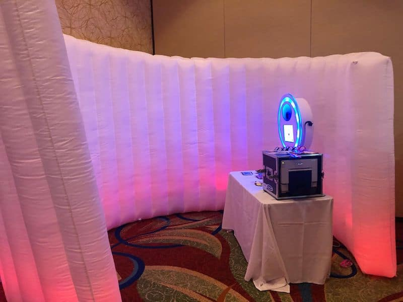 photobooth set up in corner of wedding reception with white blow up backdrop lit with red lights