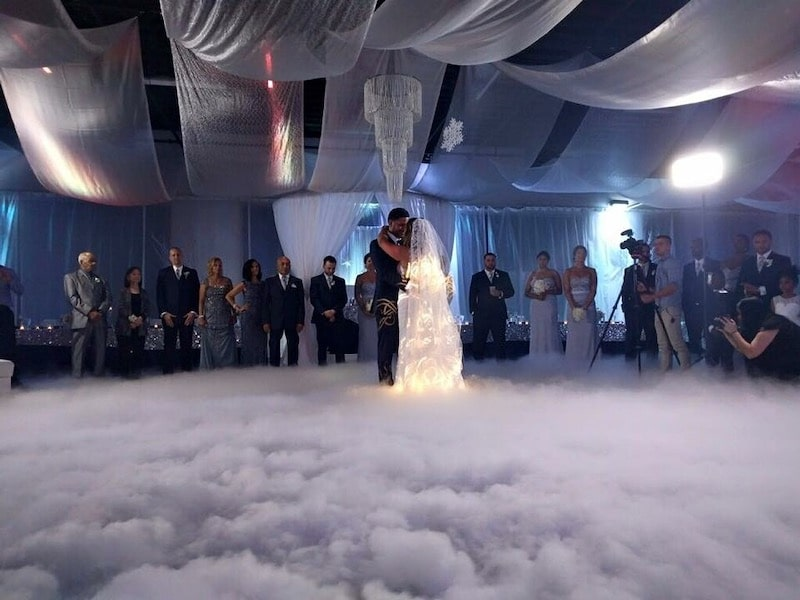 bride and groom dancing while fog lines the dance floor and guests watch