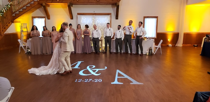 bride and groom sharing first dance while bridal party lines the dance floor behind them