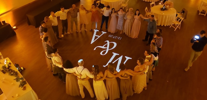 guests lined up in circle around dance floor with bride and grooms initials shining onto the dance floor