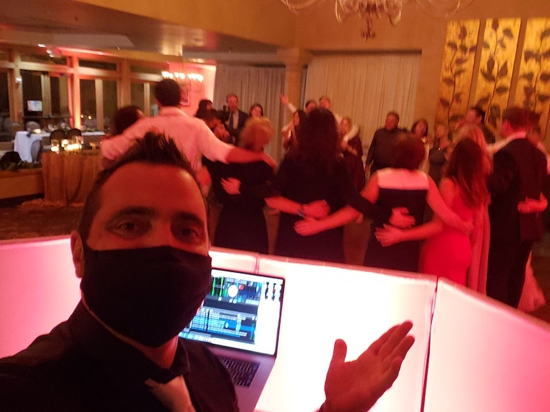 dj behind his facade with guests dancing in a circle on the dance floor